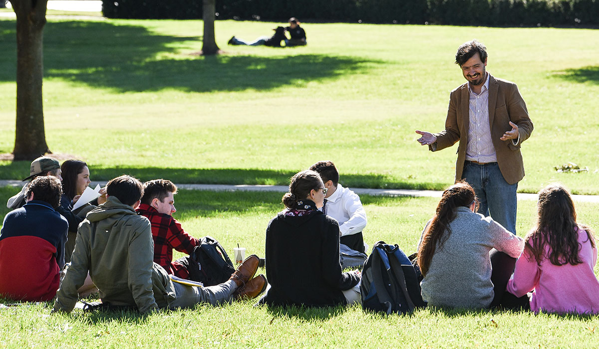 Male professor standing and teaching outside as students sit on the grass in front of him.
