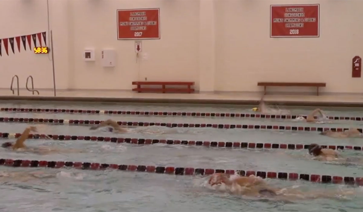 Swim teams practice in the pool at the DuFour Center while a coach gives instructions.
