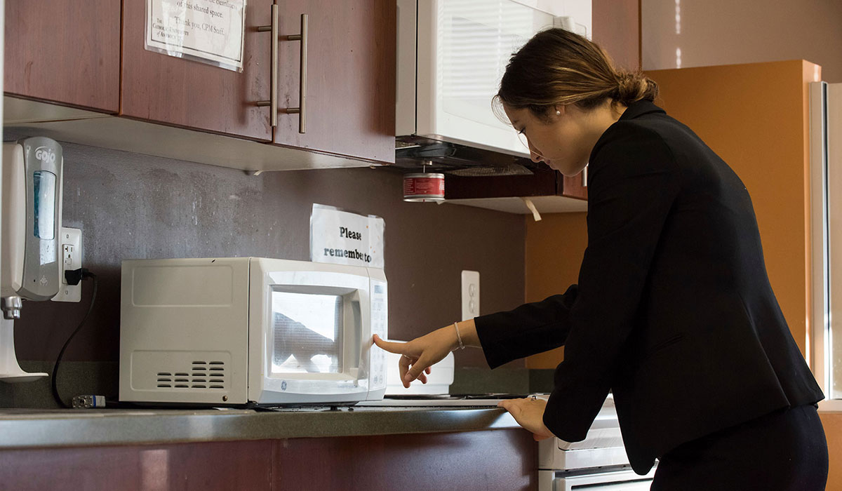 Student using microwave in residence hall room