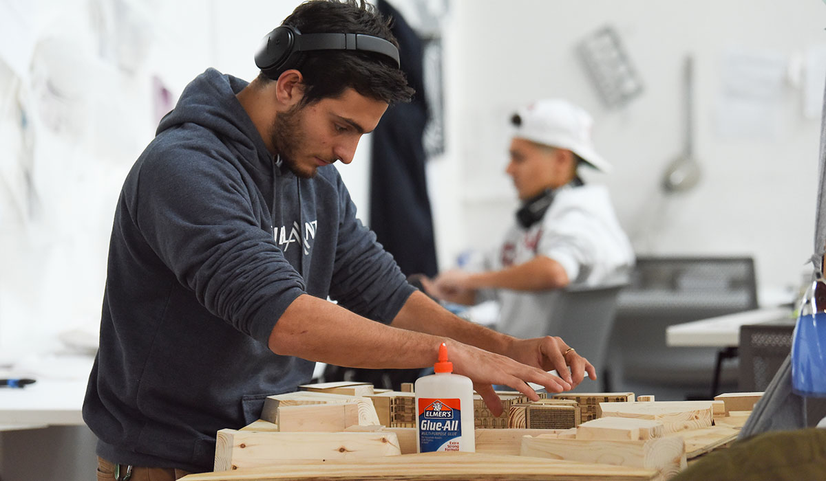 Second mosaic photo shows a male architecture student assembling a model using wood and glue