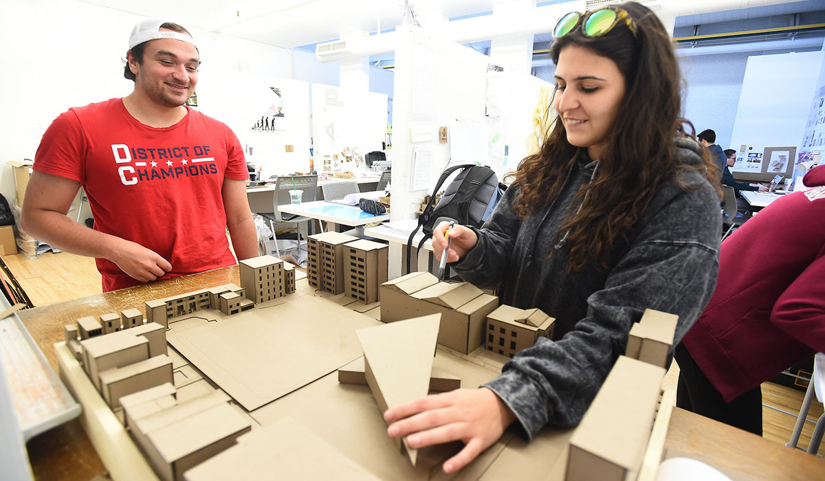 Sixth mosaic photo shows two students collaborating on a 3-D architecture project.