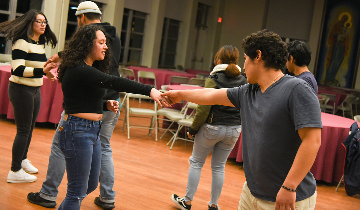 Third mosaic photo shows shows six students practicing a dance in Caldwell auditorium.