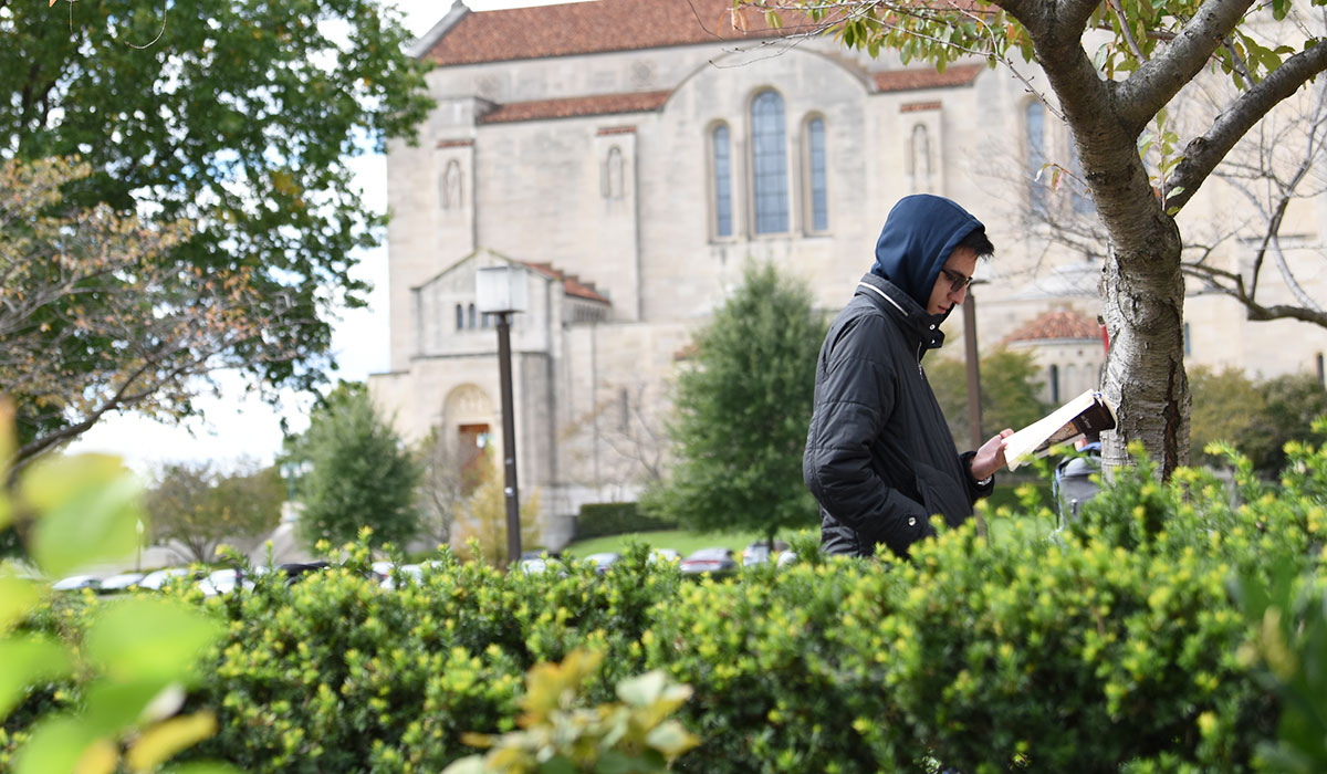 Second mosaic photo shows a male student reading a book as he walks along the University Mall with the Basilica of the National Shrine of the Immaculate Conception in the background.