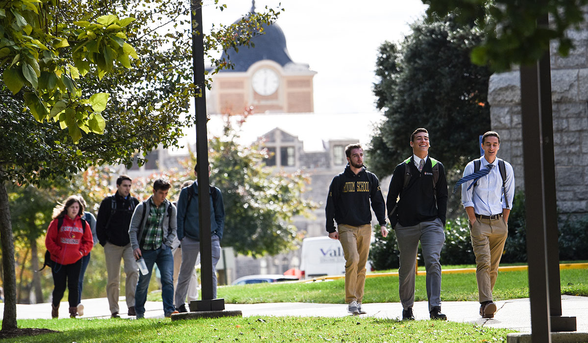 Fourth mosaic photo shows groups of students walking on the sidewalk beside McMahon Hall with the Monroe Street Market clock tower in the background.