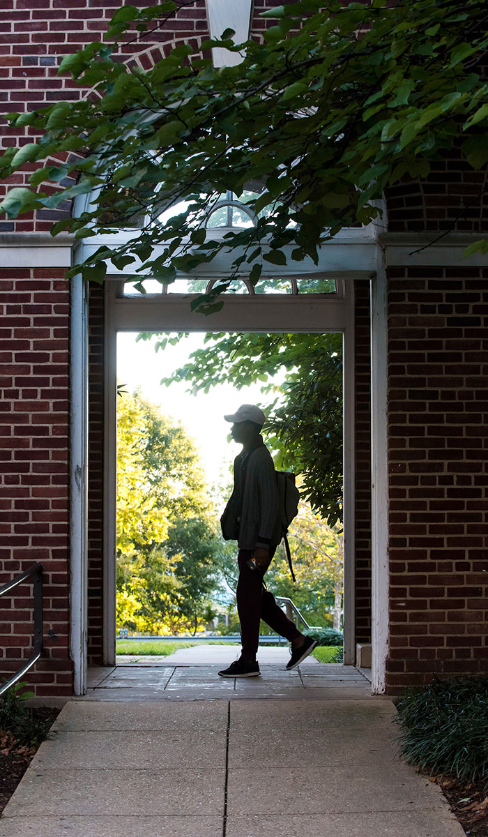 Third mosaic image shows a male student passing through archway between a residence hall on St. Vincent's Chapel.