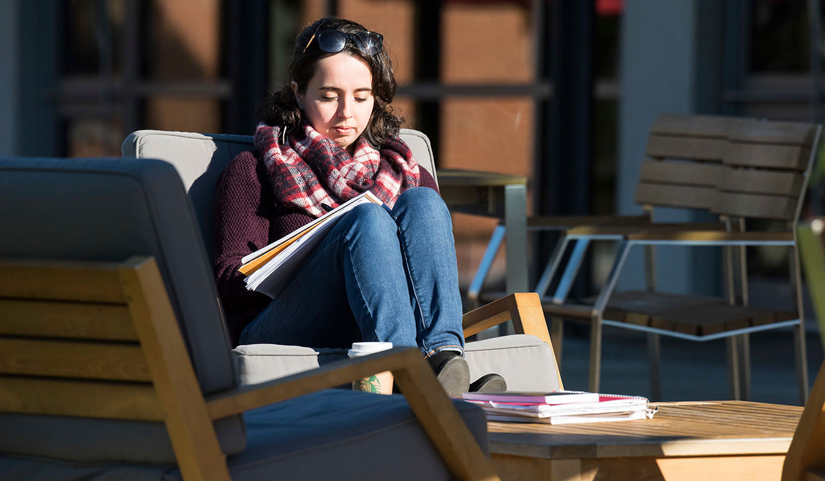 Student studying in chair outside