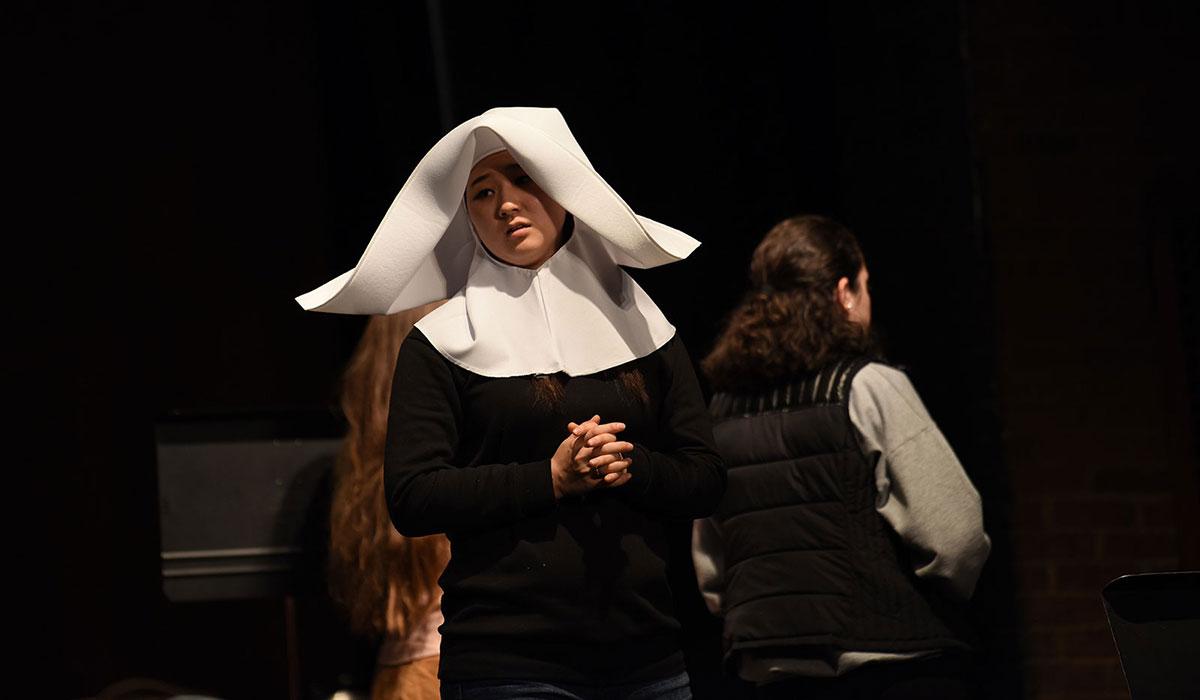Female student in religious habit singing